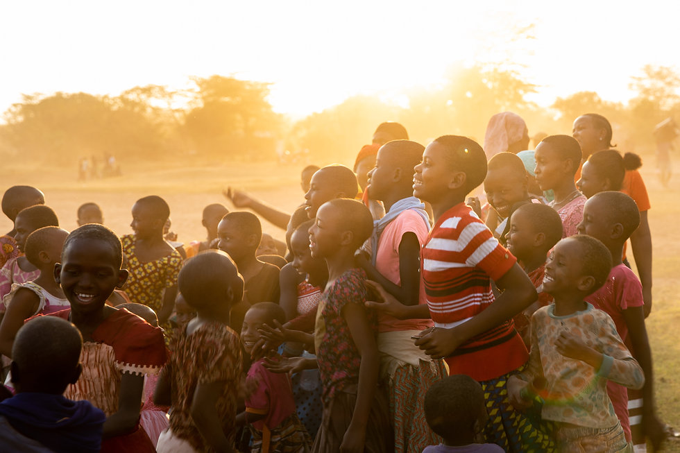children gathered on a soccer field in tanzania africa