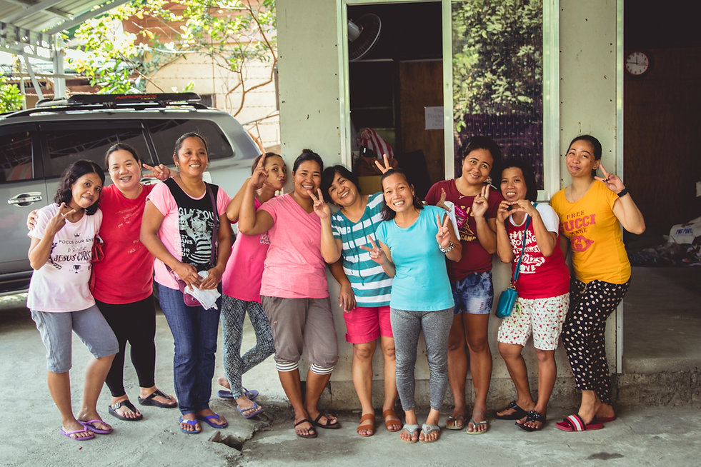 women in the philippines hold up peace signs with hands and smile