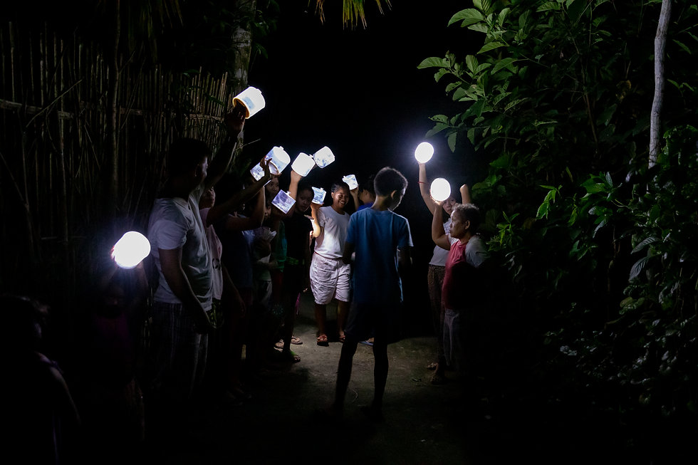 village in philippines hold up inflatable solar lights at night