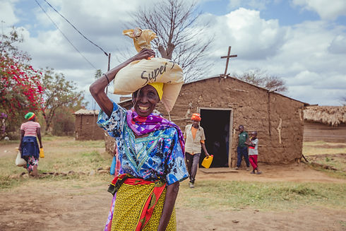 woman receives food relief in front of a church in tanzania africa during covid