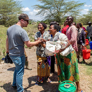 missionary shakes hands with friends during an outreach in tanzania africa