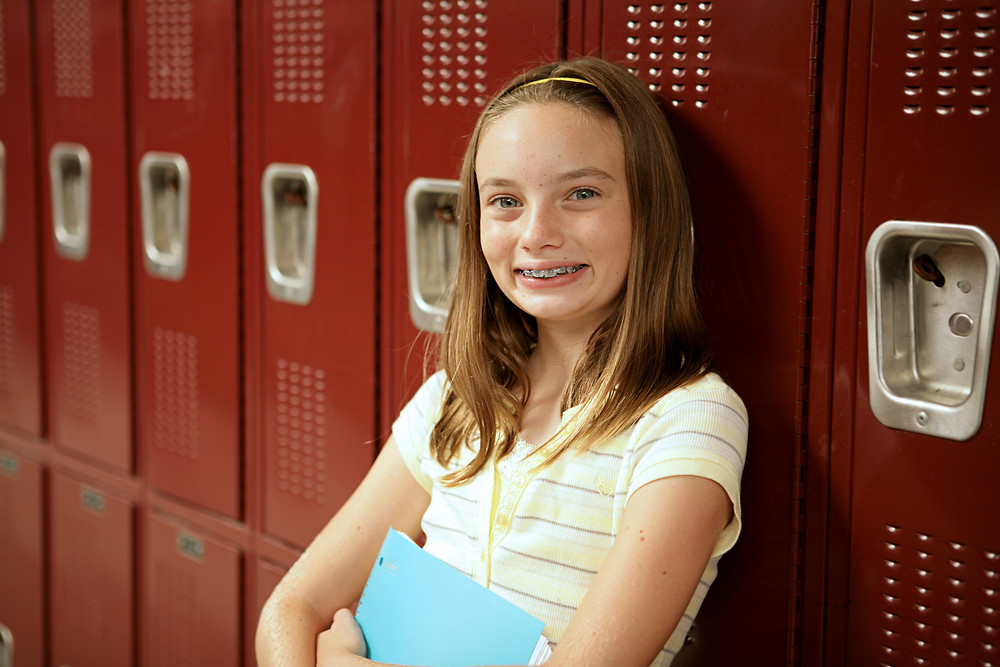 Girl in front of red lockers