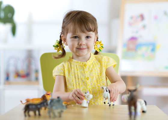Little girl playing with animal toys in