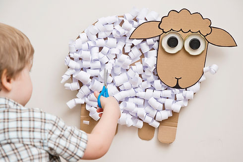 The boy cuts a paper sheep. DIY toy. Act