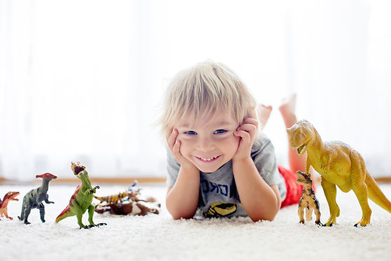 Blond toddler child, playing with dinosa