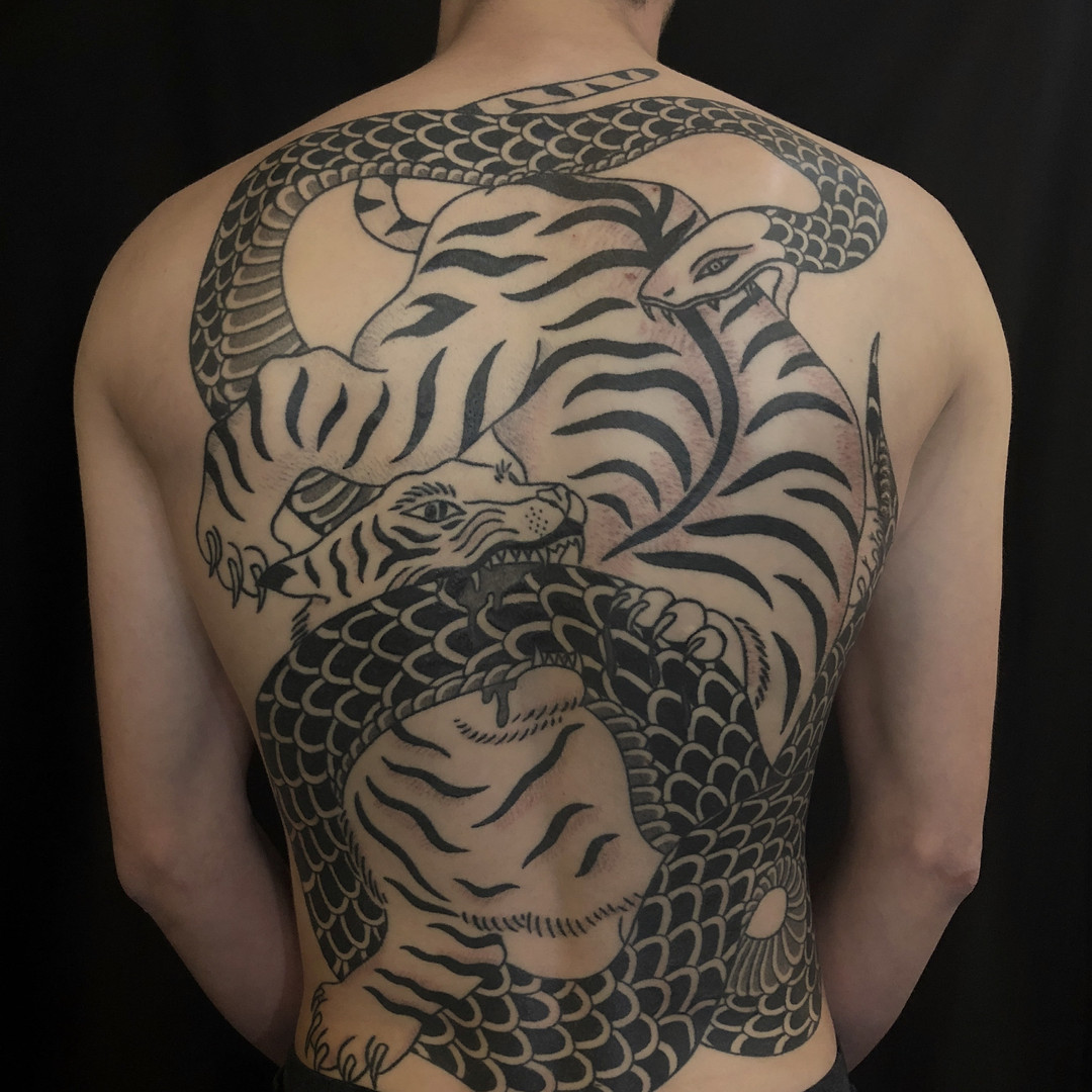 Tiger and snake fighting tattoo