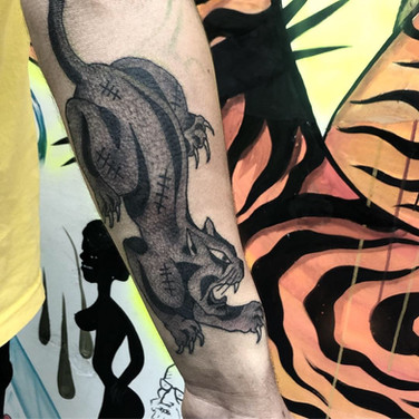 Scarred panther tattoo on forearm