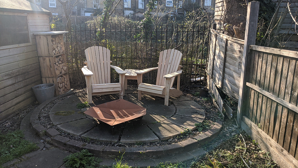 Two Adirondack chairs on a garden patio
