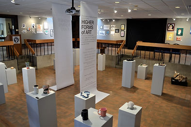 Interior view of Higher Forms of Art exhibition in the Danforth Gallery at UMA showing exhibition banners and works on pedestals