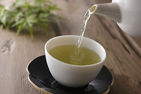 herbal-green-tea-being-poured-from-teapo
