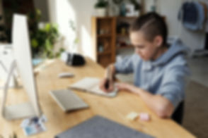 boy-in-gray-hoodie-while-writing-on-his-