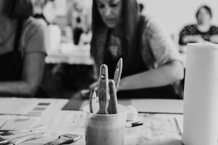 A close up of Annie Sloan paint brushes with workshop participants in the background.