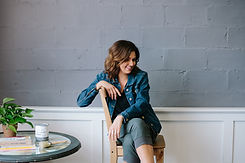 Owner, Michelle Green sitting on a chair during a photo shoot.
