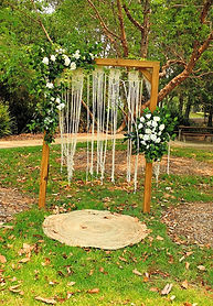 Boho wooden arbour with macrame curtain and florals