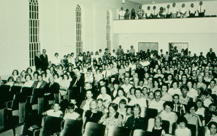 Black and white photo of the church gathered in the new auditorium, which was added to the original building.