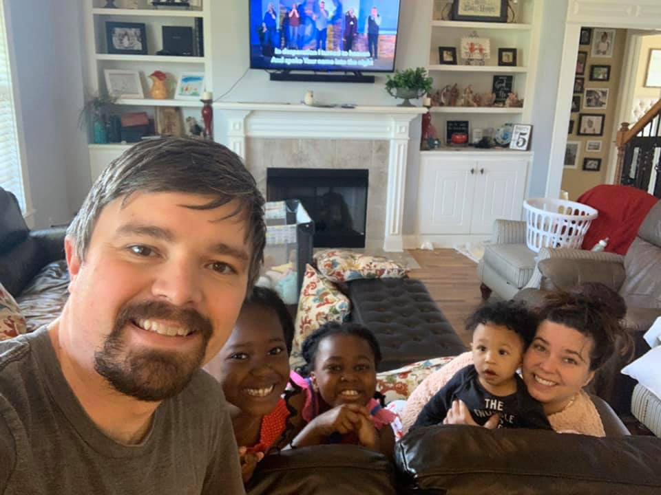 Family taking a selfie together in their living room while they are watching the Sunday morning live stream.