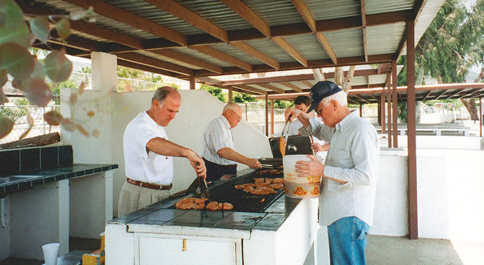 Elders grilling food to serve to the orphans at the City of Children