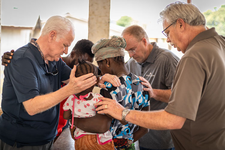 Staff members praying over an African woman and her child in Sierra Leone.