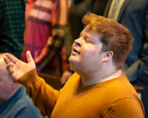 Young man with his hands raised in worship.