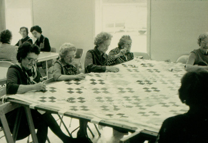 Black and white photo of elderly women sewing a quilt together.