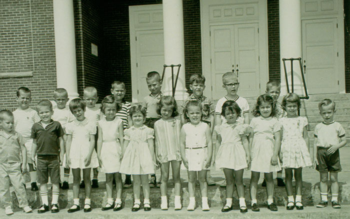 Black and white photo of children standing on the new steps of the additions made the original building.