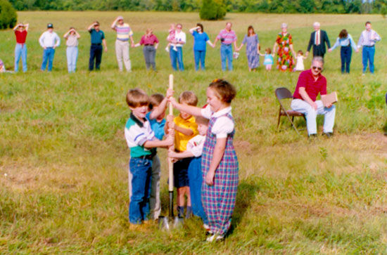 A group of children using a shovel to break ground for the new building as congregation members stand watching in the background.