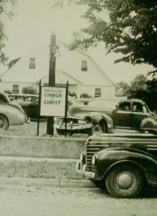 Black and White photo of cars parked outside of the Old Barn where North Boulevard was originally located on the day the church was founded.