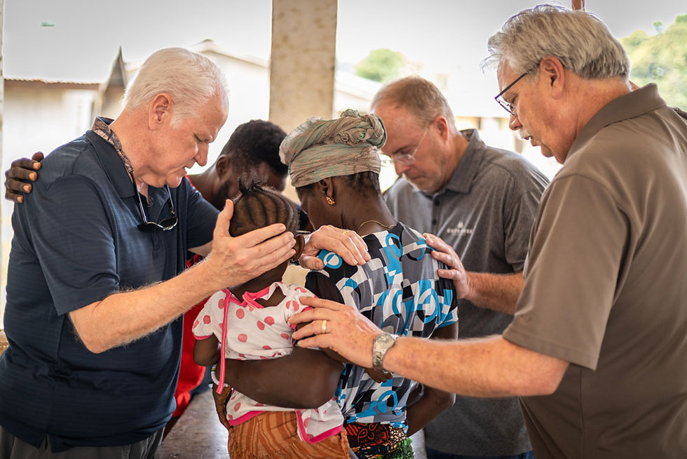 Elders and staff members praying over an African woman and her child.