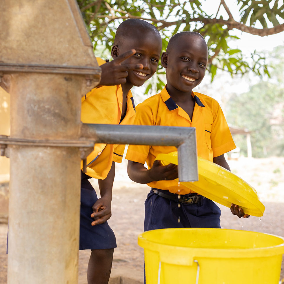 African children smiling as they fill a bucket at a water pump.