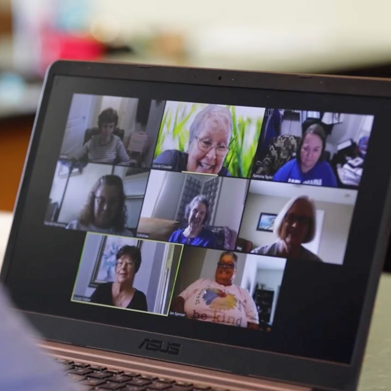 Zoom call on a laptop screen with a group of 8 women meeting for their small group discussion.