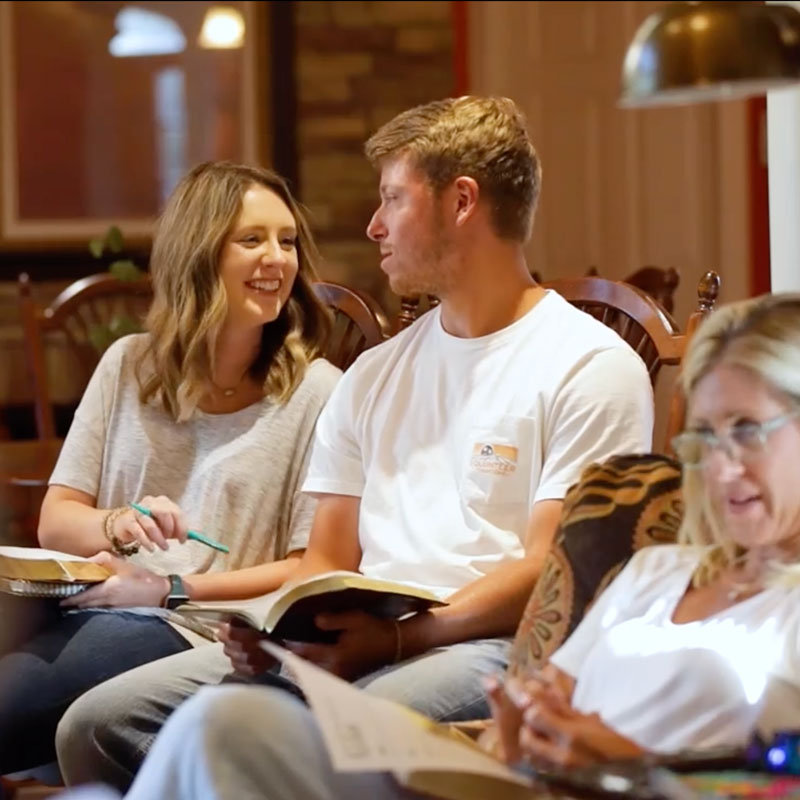 Young couple and another woman sitting and talking in a living room with their Bibles open in their laps.