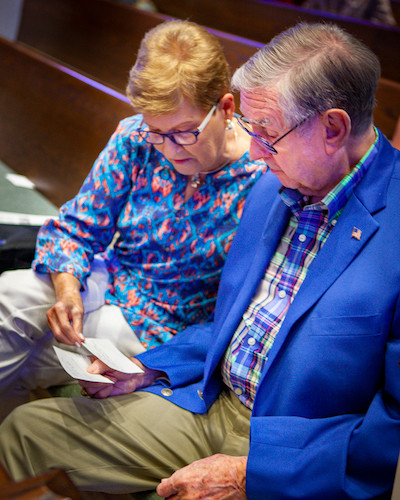 A woman wearing a colorful blouse and pants sits next to her husband wearing khakis, a button up shirt, and a suit jacket.