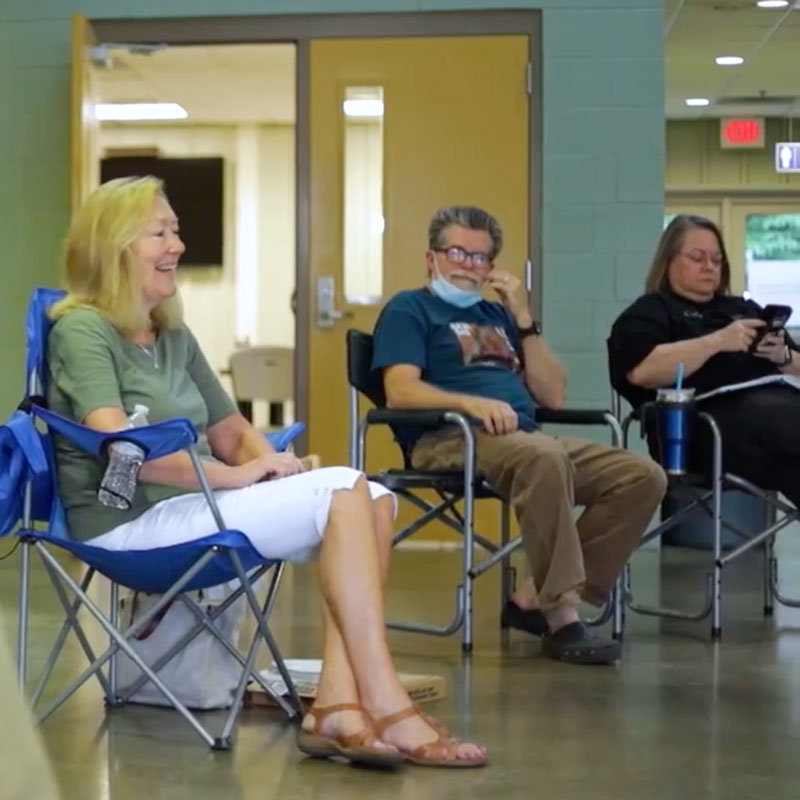 Three middle-aged adults sitting in camping chairs in a school hallway to meet with their group.