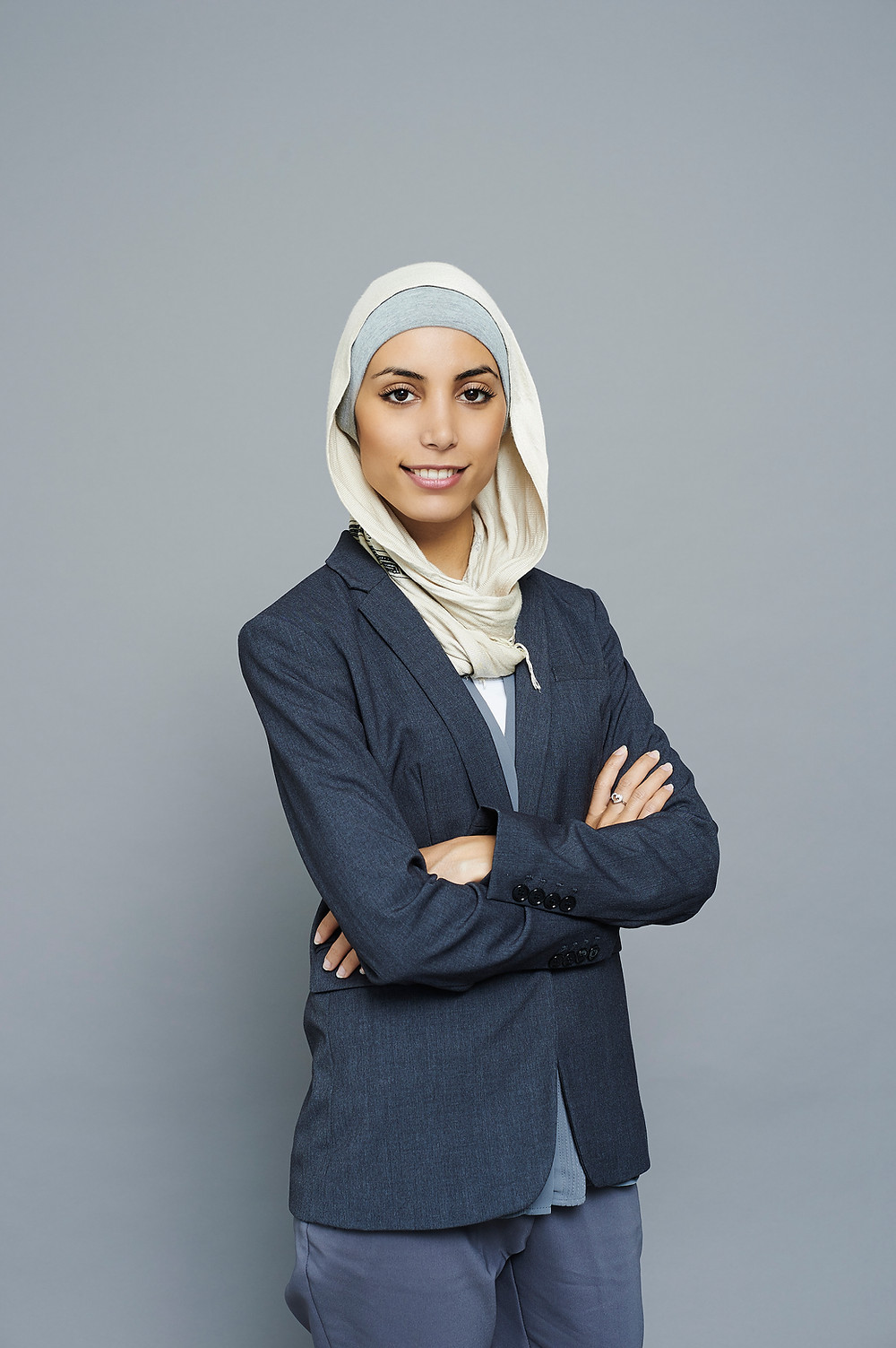 Woman in a white hijab and casual suit in front of a gray wall.