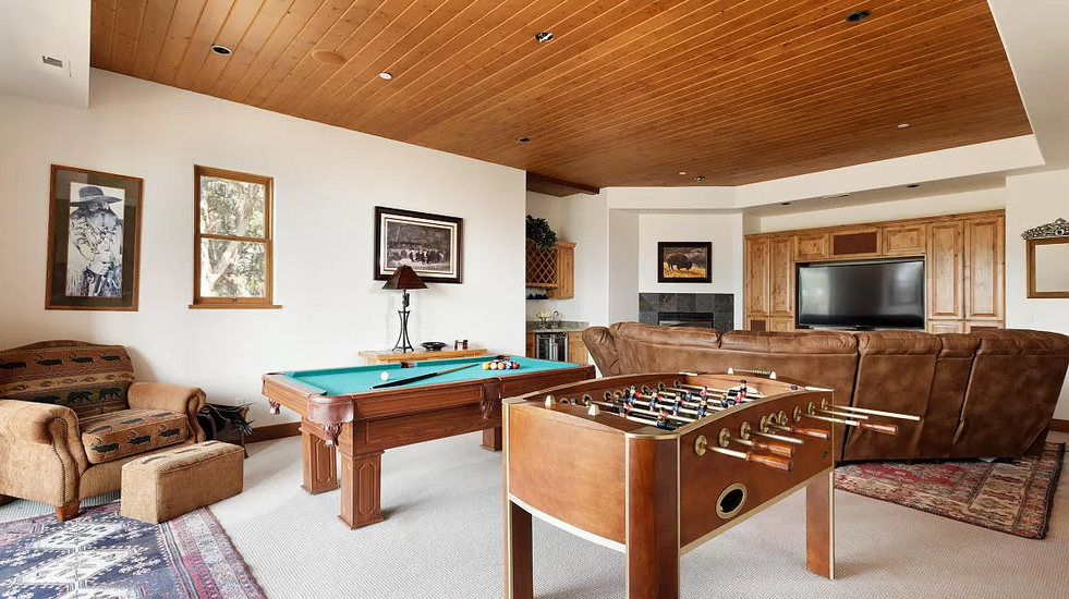 Large game room on the bottom floor with pool & foosball and television