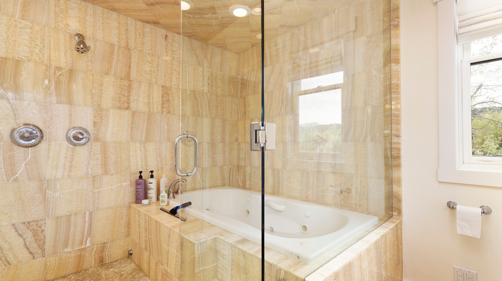 Master bathroom with steam shower and separate soaker tub.