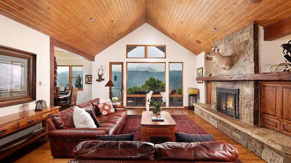 Beautiful main floor living room with fireplace, TV, and views of Mt. Sopris