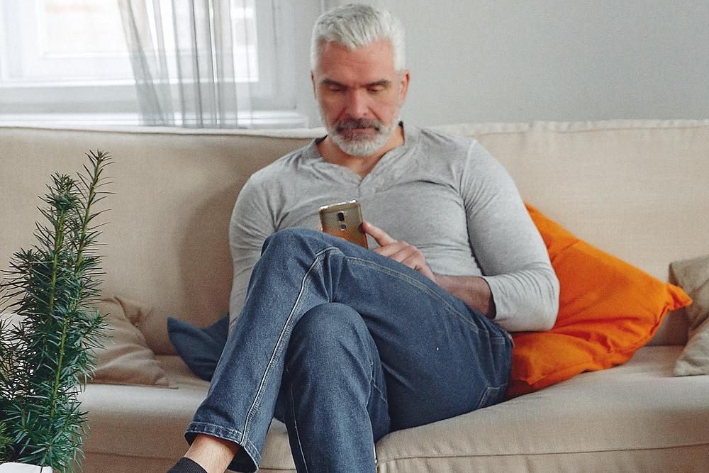 Older man on sofa cushion dent