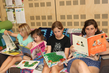 A group of three girls and a lady reading books..