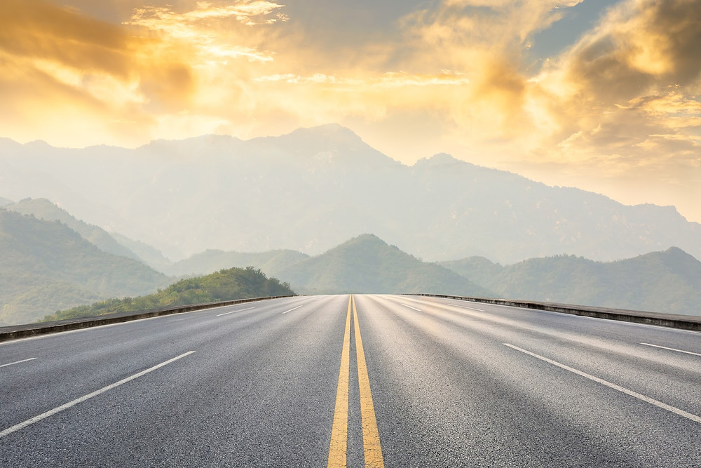 highway towards mountains with sunset