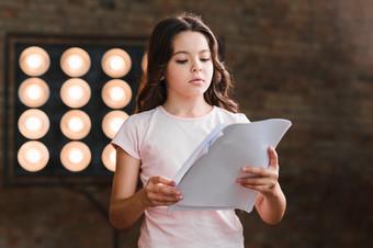 girl-reading-script-standing-against-sta