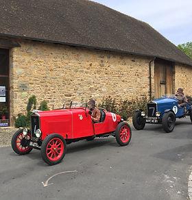 Visite d'un club de voitures anciennes. Deux voitures  rouge et bleue passent devant le musée.