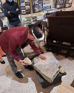Atelier broyage de minerai sur des tables gauloises pendant une visite d'un groupe handicap
