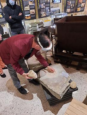 Atelier de broyage de minerai sur des tables gauloises pendant une visite adaptée handicap.