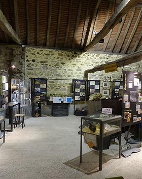 Vue de l'intérieur de la Maison de l'Or avec magnifique charpente : panneaux, maquettes, vitrines.