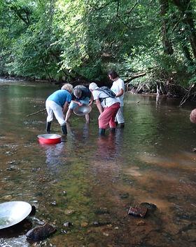 Orpaillage en rivière : trois visiteurs autour de l'orpailleur qui montre l'intérieur de sa batée.