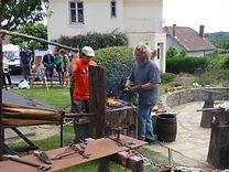 Un forgeron fait une démonstration sur la place pendant la journée métiers gaulois Chal'Art.