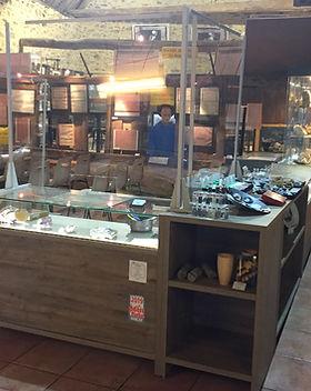 L'accueil : les   comptoirs, surplombés de plexiglass présentent des pierres et objets en vente.