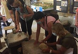 Atelier tactile broyage de minerai sur des tables gauloises lors d'une visite de déficients visuels.