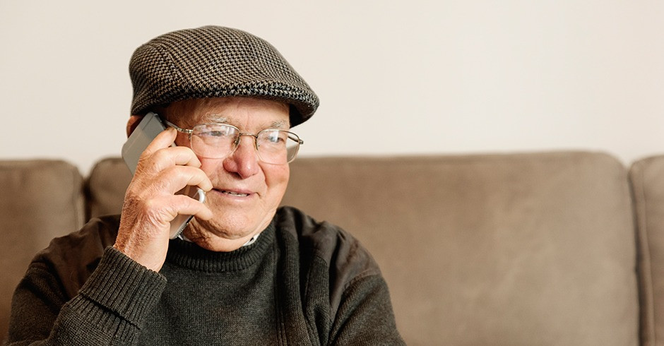 Happy older man using phone